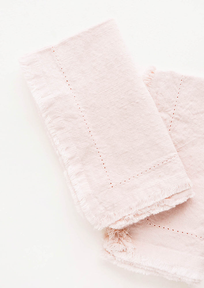 Dusty Rose: Two folded pink Cotton Napkins with frayed edges .