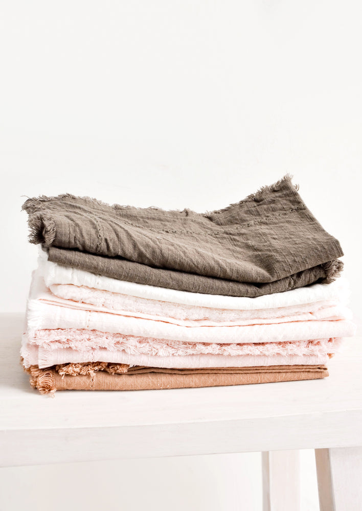 Blush: Stack of Cotton Napkins with frayed edges in browns and pinks.