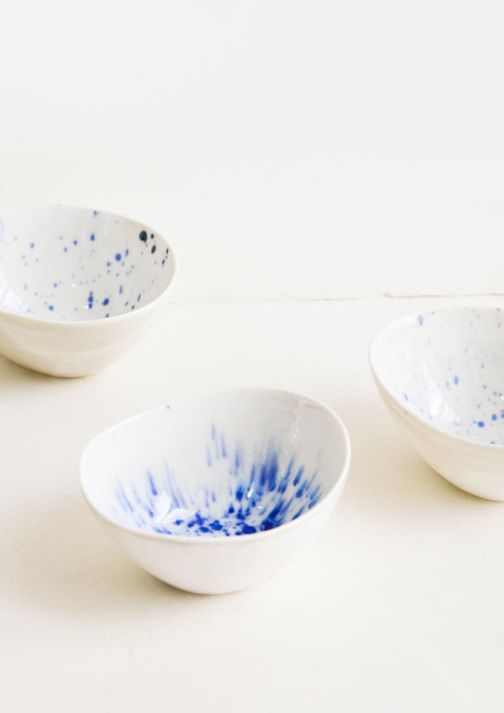 1: Small, oblong shaped ceramic bowls in white with randomized watercolor splatter pattern in blue