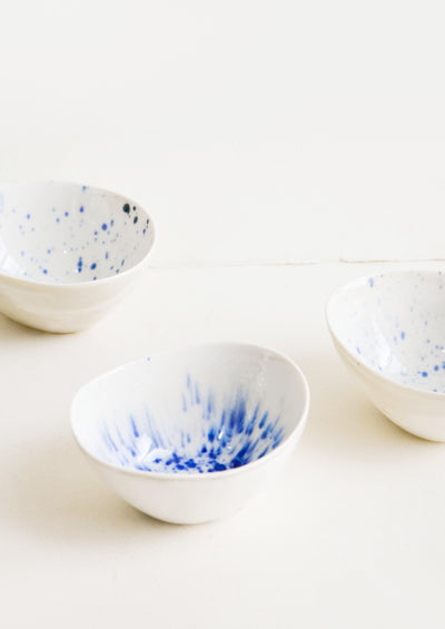 Small, oblong shaped ceramic bowls in white with randomized watercolor splatter pattern in blue