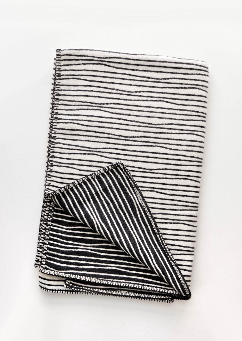 Ivory / Charcoal: Plush throw blanket with allover wavy lines print in black on white