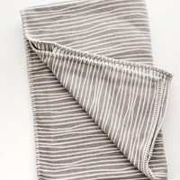 Taupe / Ivory: Plush throw blanket with allover wavy lines print in white on taupe