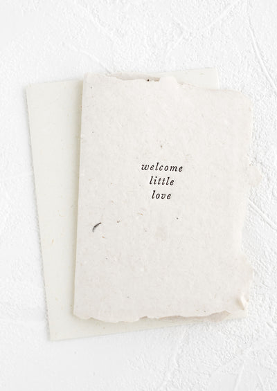 "A greeting card made from natural handmade paper and small lowercase text on front reading ""Welcome little love""."