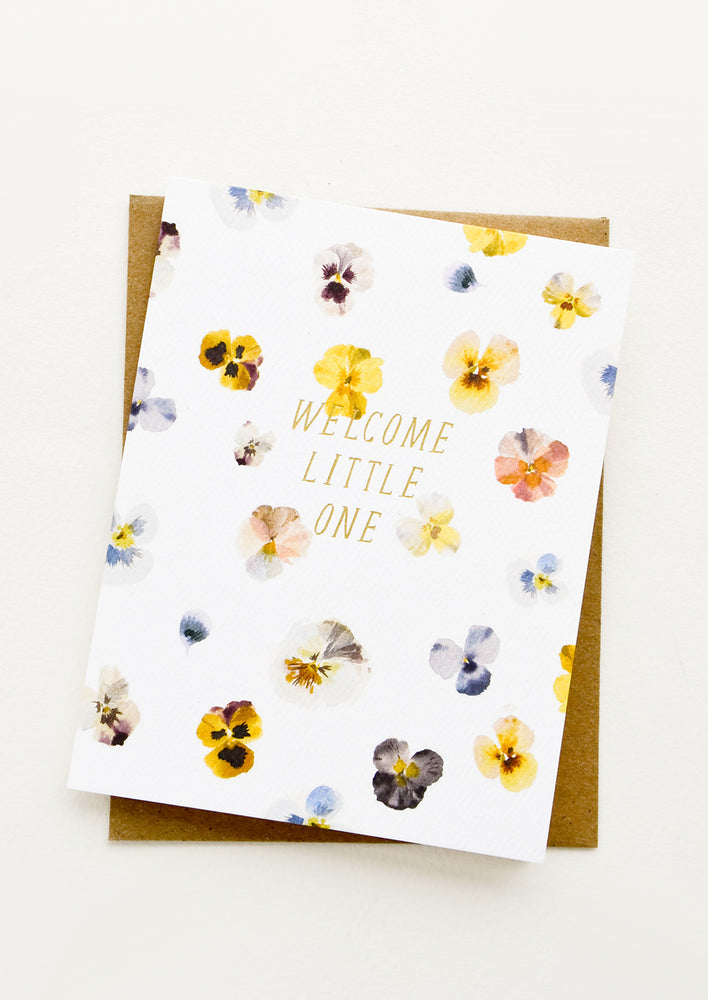 "1: Greeting card with watercolor painted pansy flowers and gold text at center reading ""Welcome Little One"""