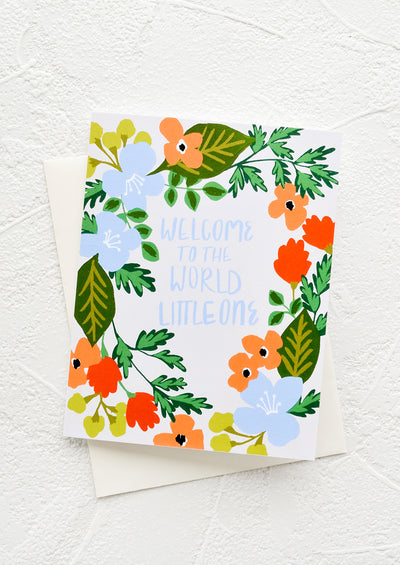 "Greeting card with floral wreath border and blue text at middle reading ""Welcome to the world little one"""