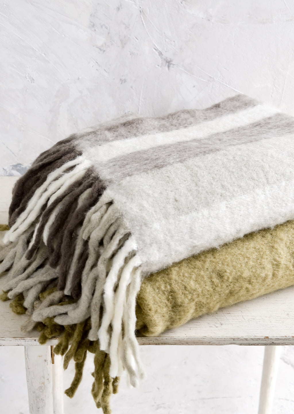 3: Two fuzzy throw blankets, stacked on a table.