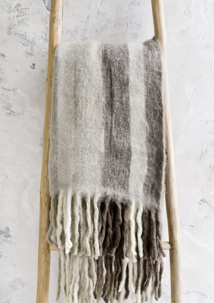 Fog Multi: A fuzzy throw blanket with exaggerated fringe in grey multi.