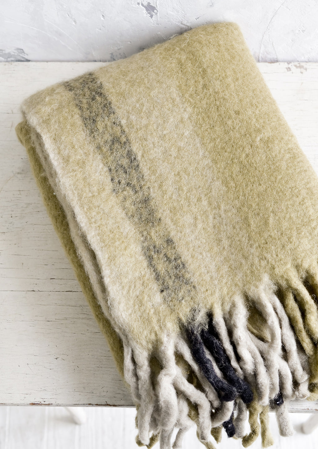Ochre Multi: A fuzzy throw blanket with exaggerated fringe in ochre multi.