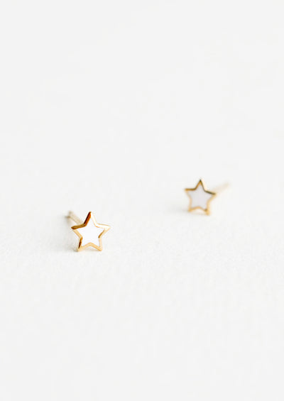 Star shaped stud earrings in white enamel outlined in yellow gold.