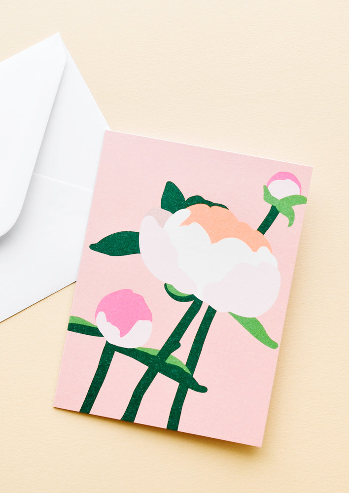 Pink notecard with colorful drawing of a peony and white envelope.