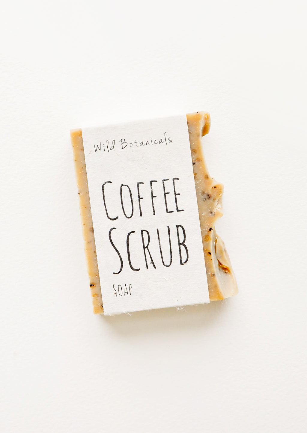Coffee Scrub: A brown bar soap with one rough edge wrapped in an unbleached paper label.