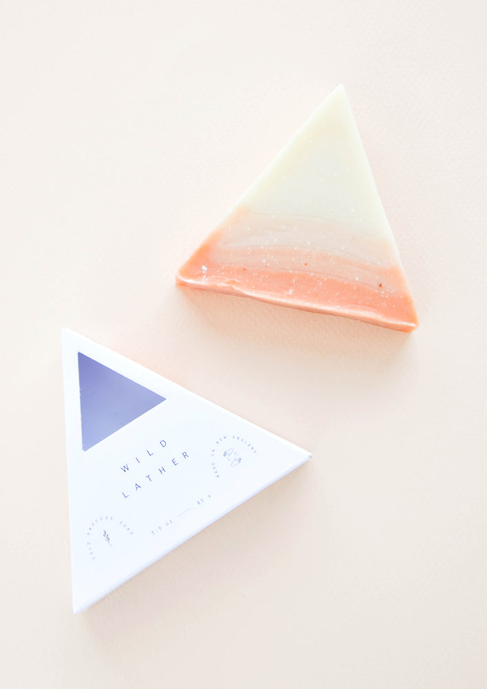 Call Me By Your Name: A pink and ivory triangular bar soap next to its triangle shaped white packaging.