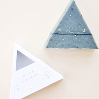 Hong Kong: A blue-gray triangular bar soap next to its triangle shaped white packaging.