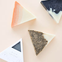 1: Four triangle-shaped bar soaps are laid out with one in white cardboard packaging.