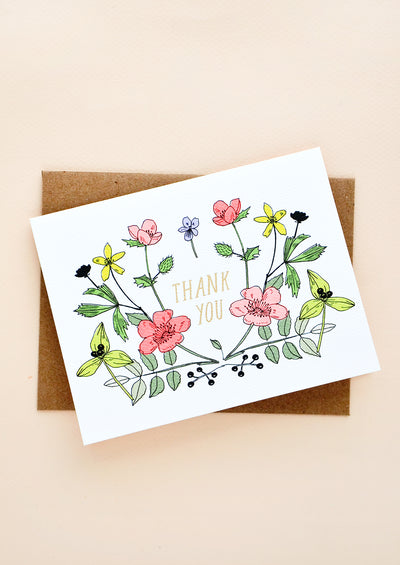 "Greeting card with colorful flowers and ""Thank you"" at center in golden letters"