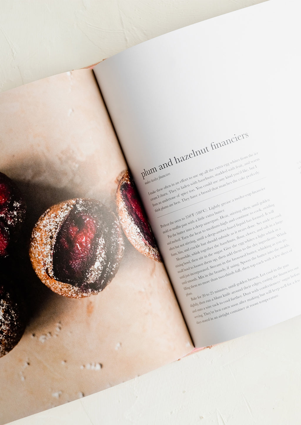 2: A recipe cookbook opened to recipe for plum and hazelnut financiers.