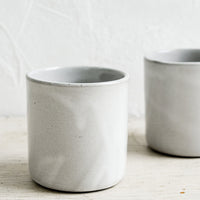 1: Two short ceramic cups in a grey glaze.