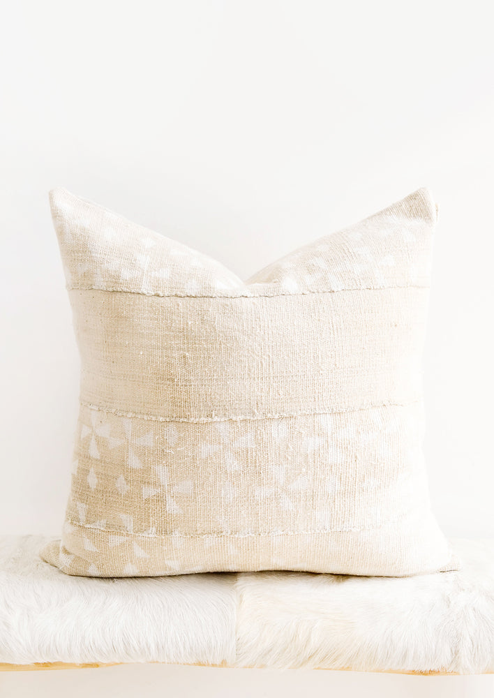 Rectangular lumbar pillow in beige mudcloth with allover white windmill pattern