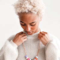 2: Model wears sweater and necklace with nine clay beads.