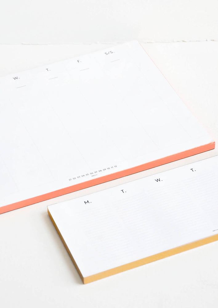 2: One small and one large desk calendar featuring one column for each day of the week, with edges painted in pink and yellow.
