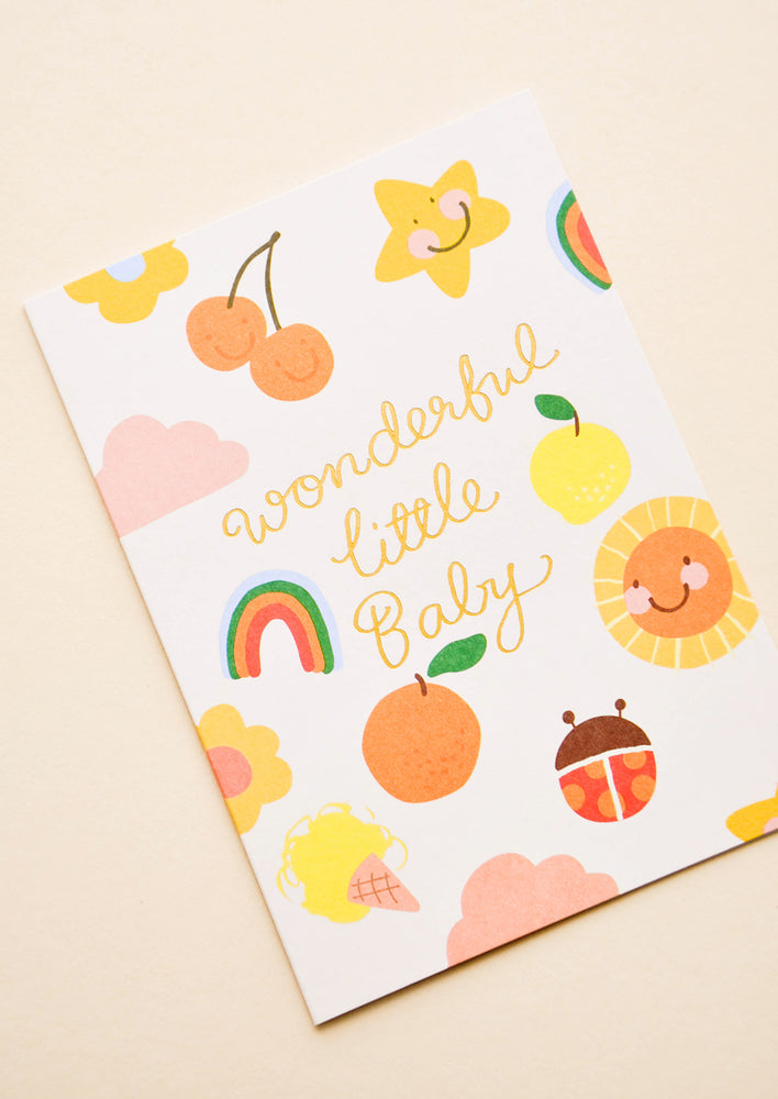 "2: Greeting card with illustrated shapes and ""Wonderful little baby"" written in gold foil."