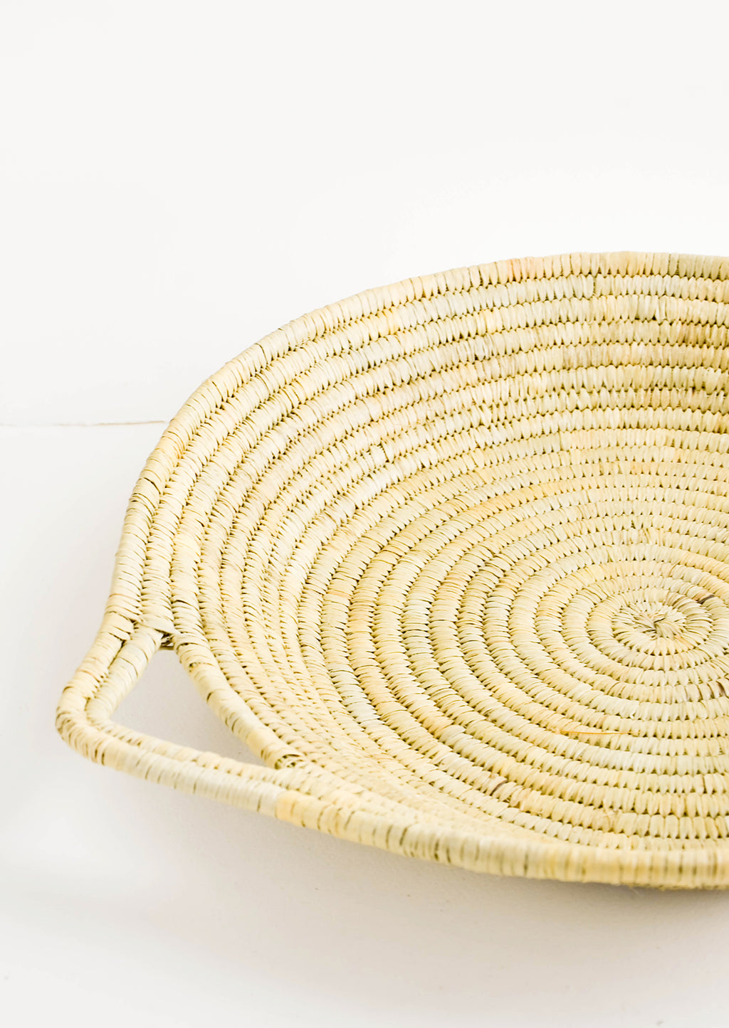 2: Flat, round platter woven from natural straw with handles at sides