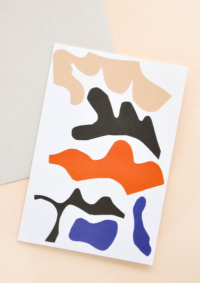 Notecard with colorful abstract shapes on white background, and grey envelope.
