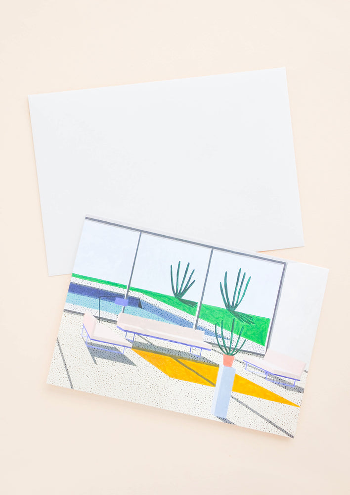 1: A white envelope and a greeting card of a colorful illustration of the interior of a modern desert house.