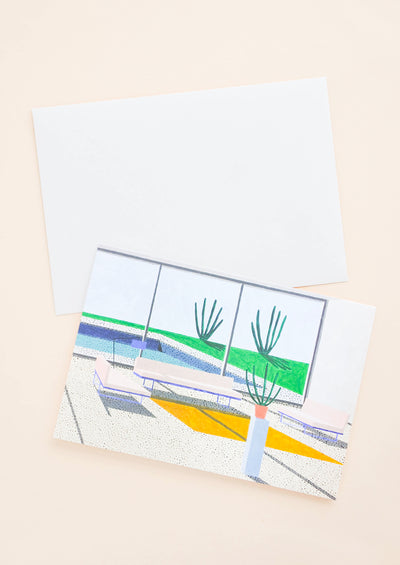 A white envelope and a greeting card of a colorful illustration of the interior of a modern desert house.