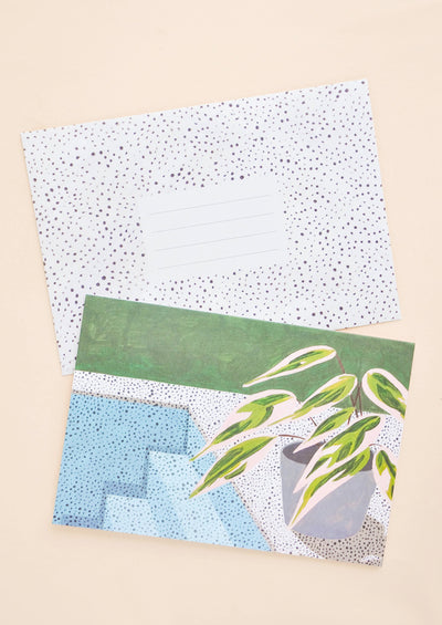 A black and white polka dot envelope and a greeting card illustrated with a simple scene of a plant by the corner of a pool.