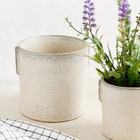 1: Two neutral ceramic planters in small and large sizes with lavender plant.