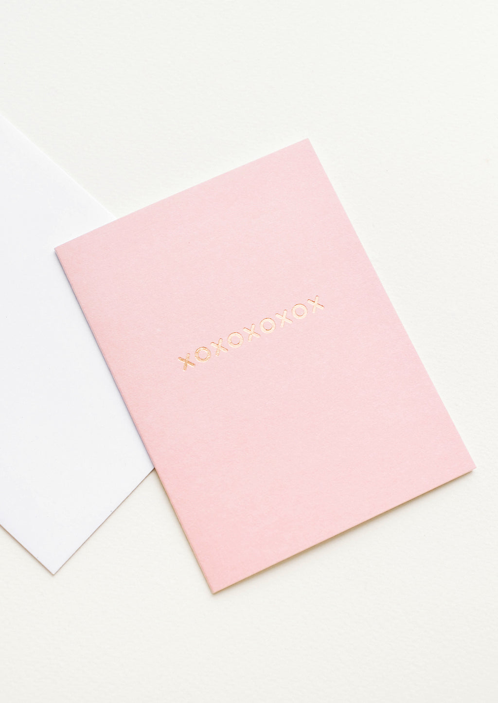 "2: A white envelope and pale pink greeting card with ""xoxoxoxoxox"" in gold foil."