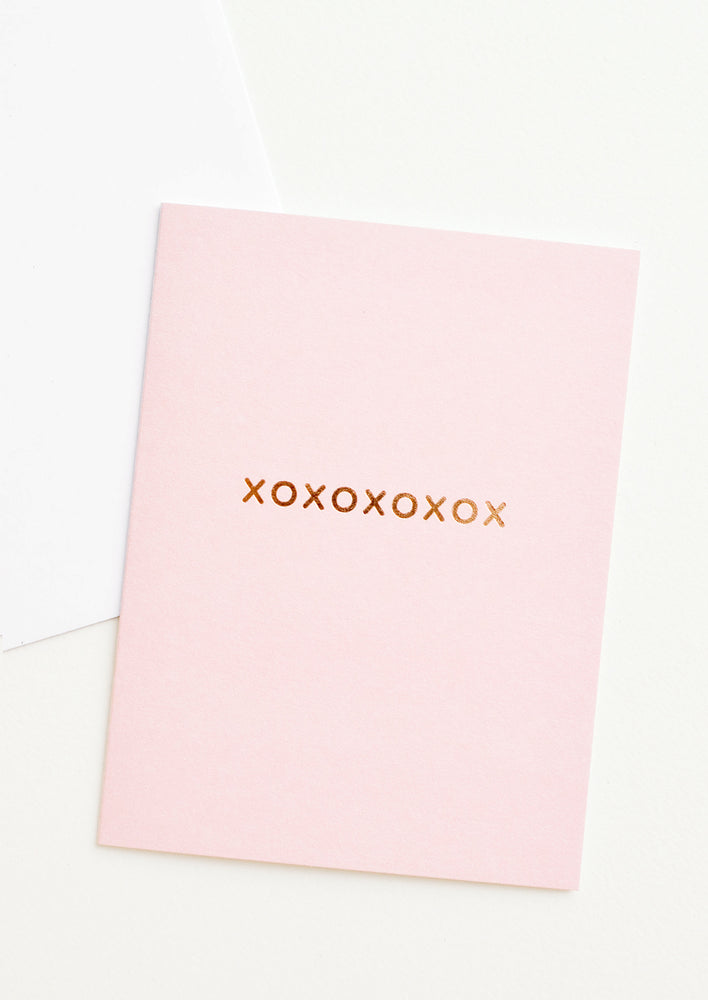 "1: A pale pink greeting card with ""xoxoxoxoxox"" in gold foil."