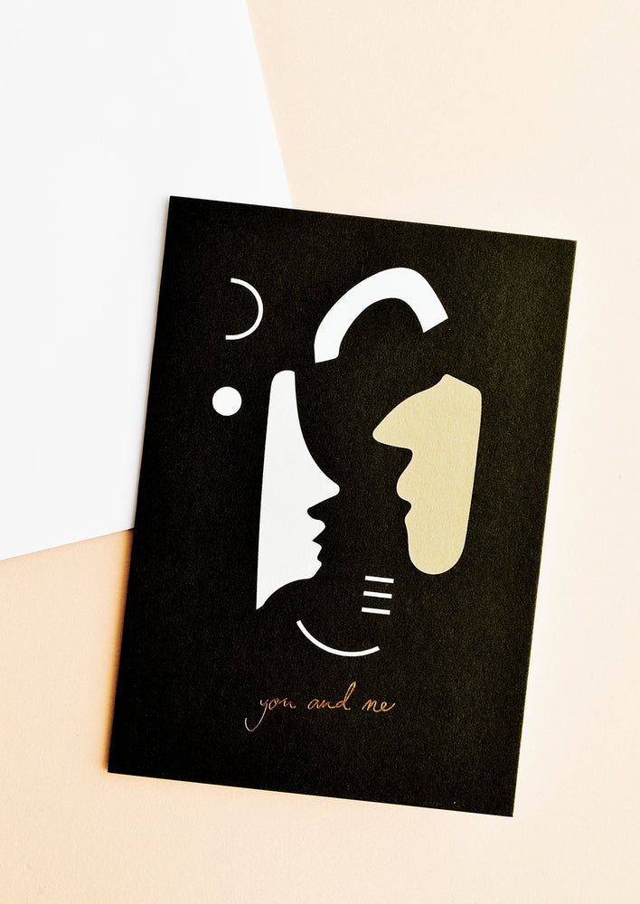 "1: Black greeting card with abstract and human-like shapes in white and brown with the text ""you and me"" at bottom."
