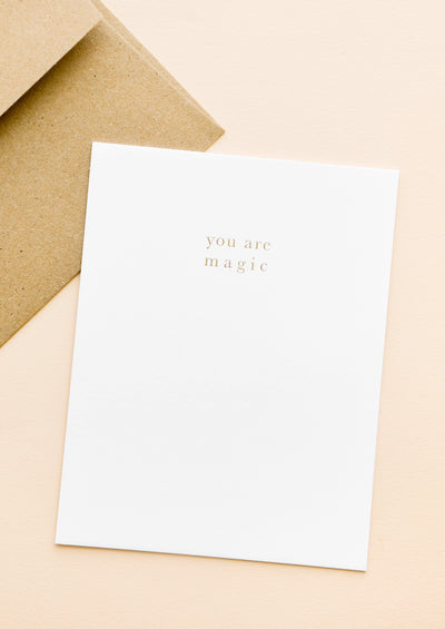 "A brown paper envelope and white greeting card with the words ""you are magic"" in small gold text."