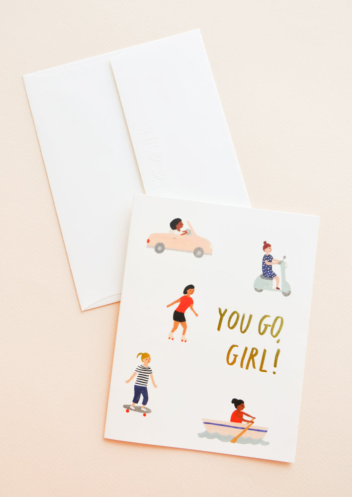 "1: A white envelope and a greeting card with little illustrations of women in motion and the words ""you go girl"" in gold foil."