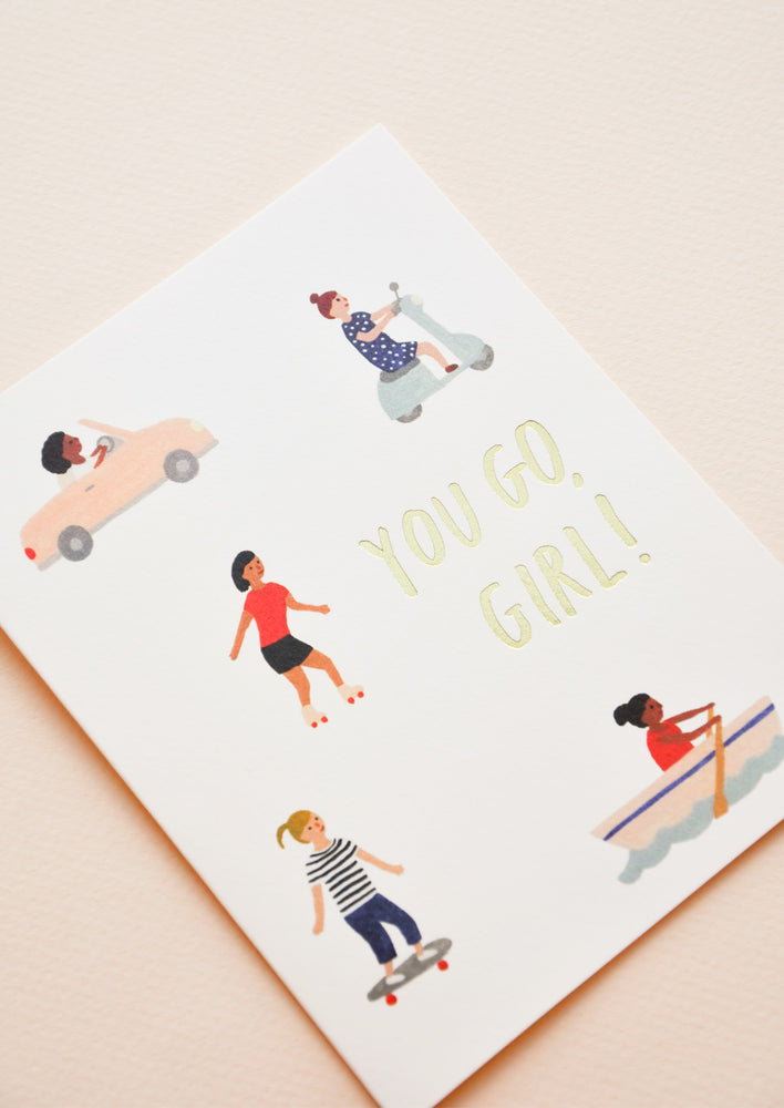 "2: A greeting card with little illustrations of women in motion and the words ""you go girl"" in gold foil."