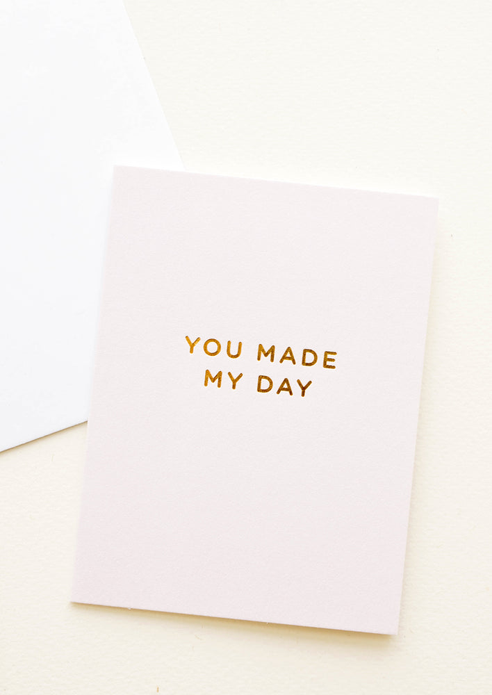 "1: A white envelope and a light tan greeting card with the words ""you made my day"" in gold foil."