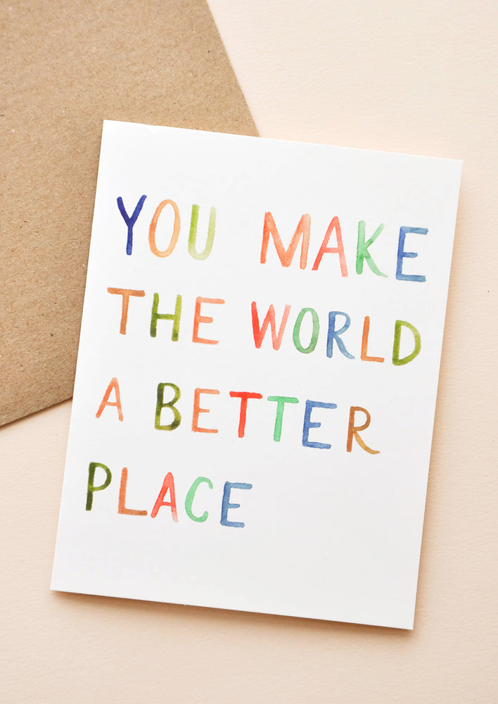"1: White notecard with rainbow painted text ""You Make The World A Better Place Card"" with brown envelope."