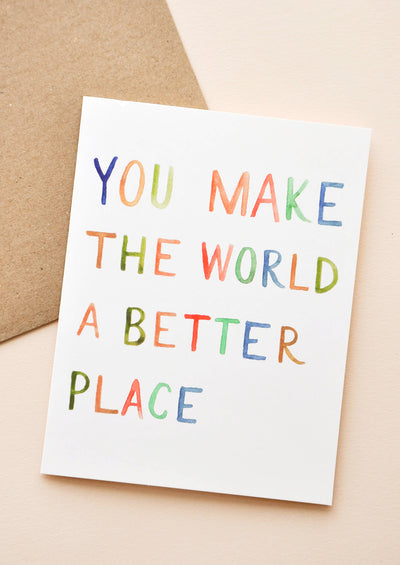 "White notecard with rainbow painted text ""You Make The World A Better Place Card"" with brown envelope."