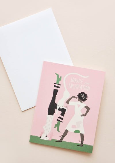 "A white envelope and a pink greeting card depicting two women and a cat with the words ""you're an inspiration."""