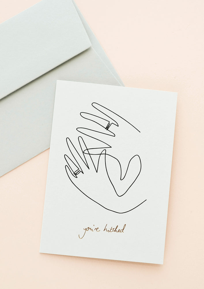 "1: White greeting card with sketch of hands showing off wedding bands. ""You're Hitched"" written in gold foil. Shown with grey envelope."