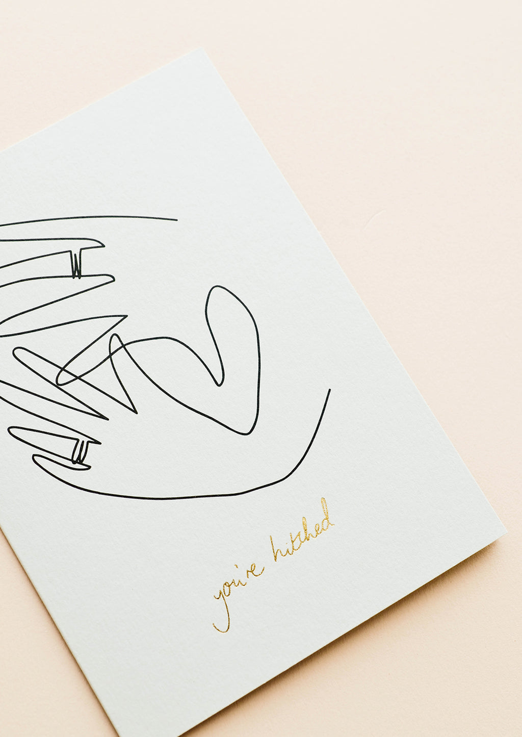 "2: White greeting card with sketch of hands showing off wedding bands. ""You're Hitched"" written in gold foil."