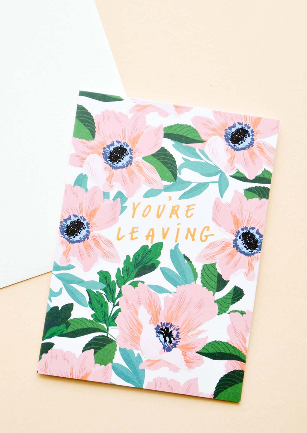 "1: White greeting card with large pink flowers. ""You're leaving"" written in gold text."