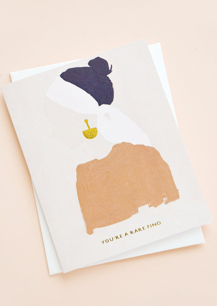 "1: Greeting card with silhouetted image of a woman wearing gold earrings, gold text below reads ""You're A Rare Find"""