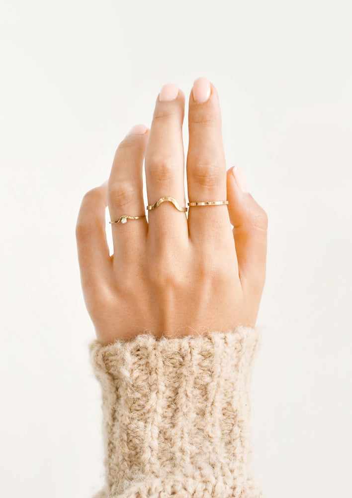 2: Model shot of hand wearing three different styles of rings.