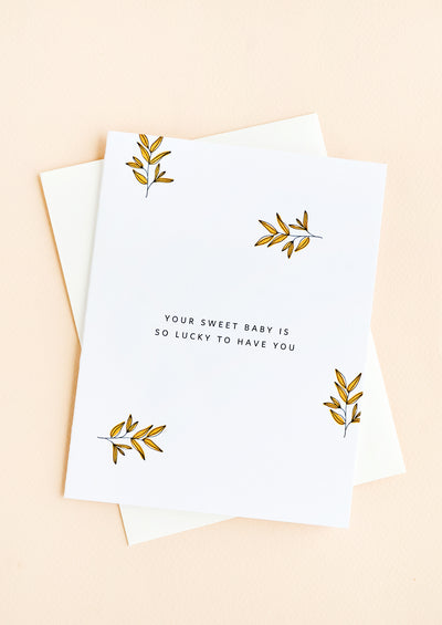 "A greeting card with scattered leaf print and small caps text reading ""Your sweet baby is so lucky to have you"""