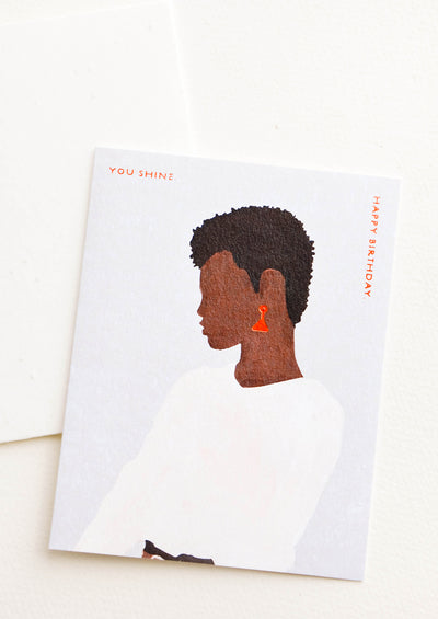 "Greeting card with silhouetted profile of a woman wearing earrings, copper text reads ""You Shine. Happy Birthday"""