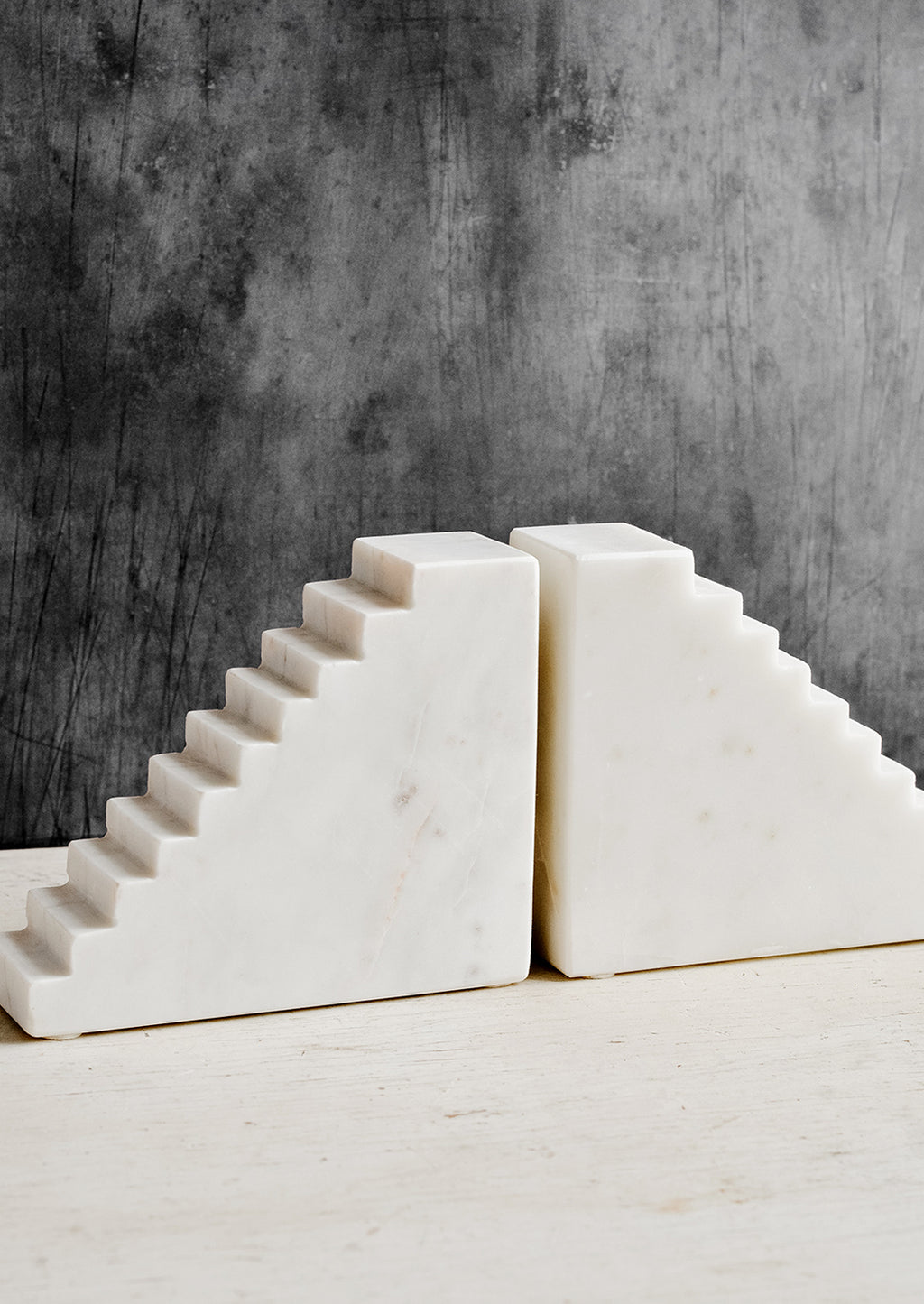1: A pair of white marble bookends with staircase design.