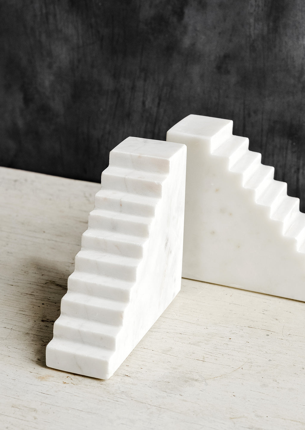 3: A pair of white marble bookends with staircase design.